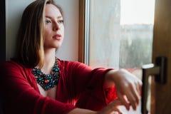 Schönes sexy Mädchen in einer roten Robe sitzt auf dem Fensterbrett zu Hause Stockbilder