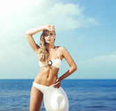 Schönes, sexy Mädchen im anziehenden Bikini, der mit einem Hut auf aufwirft Lizenzfreie Stockbilder