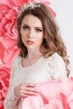 Schönes sexy Mädchen im langen Kleid mit den enormen rosa Blumen, die am Fenster sitzen Lizenzfreie Stockbilder