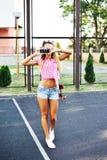 Schönes Mädchen kurz gesagt und Sonnenbrille aufwerfend mit altem Nocken Stockbilder