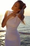 Schönes sexy Mädchen mit dem blonden Haar im eleganten Kleid, das auf Yacht aufwirft lizenzfreies stockbild