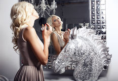 Schönes sexy Mädchen mit dem Parfüm, das den Spiegel betrachtet Lizenzfreies Stockbild