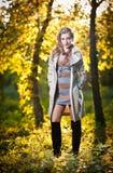 Schönes Mädchen mit langen Lederstiefeln und Kurzschluss kleiden die Aufstellung im Park am Herbsttag. Lizenzfreies Stockfoto