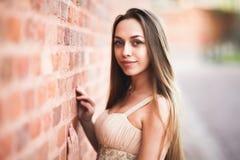 Schönes sexy Mädchen mit langer perfekter Form des Haares und des Kleides bräunte den Körper, der nahe Wand possing ist Stockbilder