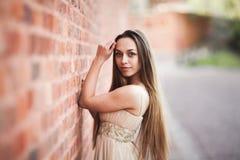 Schönes sexy Mädchen mit langer perfekter Form des Haares und des Kleides bräunte den Körper, der nahe Wand possing ist Lizenzfreie Stockfotos