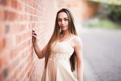 Schönes sexy Mädchen mit langer perfekter Form des Haares und des Kleides bräunte den Körper, der nahe Wand possing ist Lizenzfreie Stockfotografie