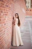 Schönes sexy Mädchen mit langer perfekter Form des Haares und des Kleides bräunte den Körper, der nahe Wand possing ist Lizenzfreie Stockbilder
