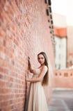 Schönes sexy Mädchen mit langer perfekter Form des Haares und des Kleides bräunte den Körper, der nahe Wand possing ist Stockfoto