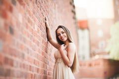 Schönes sexy Mädchen mit langer perfekter Form des Haares und des Kleides bräunte den Körper, der nahe Wand possing ist Lizenzfreies Stockfoto