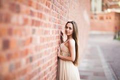 Schönes sexy Mädchen mit langer perfekter Form des Haares und des Kleides bräunte den Körper, der nahe Wand possing ist Stockfotos