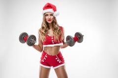 Schönes sexy Mädchen in Weihnachtsmann kleidet das Handeln des Trainings stockbilder