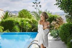 Schönes, sexy, modernes blondes Mädchen im peignoir, das halb nackten nahen Swimmingpool aufwirft Stockfoto