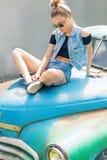 Schönes nettes Mädchen in den Denimkurzen hosen und -weste in der Sonnenbrille sitzt ein altes verlassenes blaues Auto Stockbild