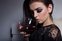 Schönes süßes Mädchen mit dem volle Lippenhellen Make-up, das auf dem Sofa mit einem Glas Wein in einem schwarzen Abendkleid Stockfoto