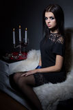 Schönes süßes Mädchen mit dem volle Lippenhellen Make-up, das auf dem Sofa mit einem Glas Wein in einem schwarzen Abendkleid Stockfotografie