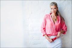 Schönes sexy sinnliches blondes Mädchen in der rosa Jacke im Stu lizenzfreie stockbilder