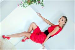Schönes sexy sinnliches blondes Mädchen mit blauen Augen in einem roten Kleid Lizenzfreie Stockfotos