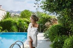 Schönes, sexy, sinnliches und heißes blondes vorbildliches Mädchen im peignoir, das halb nackten nahen Swimmingpool aufwirft Lizenzfreie Stockfotos