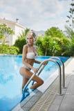 Schönes, sexy und modernes blondes Mädchen in der Wäsche, die draußen im Swimmingpool aufwirft Stockbilder