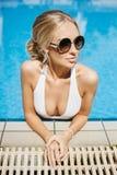 Schönes, sexy und modernes blondes vorbildliches Mädchen im Bikini und in der runden Sonnenbrille werfen im Swimmingpool auf Stockfotografie