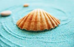 Schönes Shell und Steine auf einem blauen Sand Stockfoto