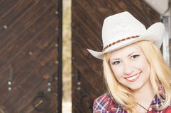Schönes sinnliches lächelndes glückliches blondes Cowgirl, das Stetson trägt Lizenzfreie Stockfotos
