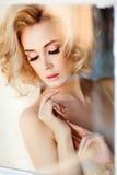 Schönes sinnliches und sexy blondes Mädchen, das am Klavier sitzt und Lizenzfreie Stockbilder