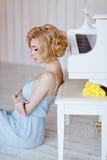 Schönes sinnliches und sexy blondes Mädchen in einem blauen Kleid, das a sitzt Lizenzfreie Stockfotos