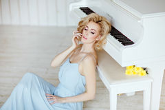 Schönes sinnliches und sexy blondes Mädchen in einem blauen Kleid, das a sitzt Stockfotografie