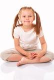 Schönes Sitzen und Lächeln des kleinen Mädchens lizenzfreies stockfoto