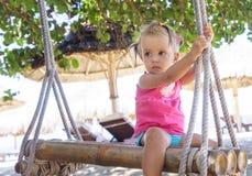 Schönes sitzendes Seil des kleinen Mädchens schwingt auf dem Strand Lizenzfreies Stockbild