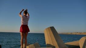 Schönes Sitzmädchen kurz gesagt tanzend auf Betonblöcke nahe dem Meer stock video footage