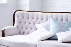 Schönes Sofa mit Kissen in einem hellen Raum lizenzfreie stockbilder