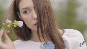 Schönes sorgloses Mädchen des Porträts, welches das lange Sommermodekleid betrachtet überzeugt der Kamera genießt Stände auf träg stock footage
