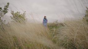 Schönes sorgloses Mädchen, welches das lange Sommermodekleid betrachtet überzeugt der Kamera genießt Stände auf dem Feld trägt stock footage