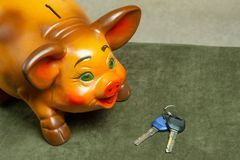 Schönes Sparschwein auf einem grünen Hintergrund und Hausschlüsseln lizenzfreies stockbild