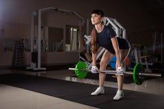 Schönes Sporteignungsmädchen mit einem Barbell Stockbild