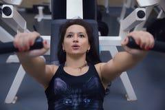 Schönes sportliches Mädchen, das auf den Simulator stützt Gestaltmuskel a Stockfoto