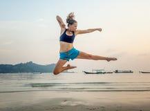 Schönes sportliches Mädchen, das auf den Strand gegen das Meer springt stockfotos