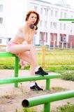 Schönes sportliches rothaariges Mädchen strebt herein Sport in der Straße mit einem Metalldummkopf an Stockfoto