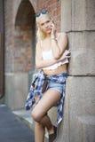 Schönes städtisches junges Mädchen, das im Telefon spricht Lizenzfreie Stockfotografie