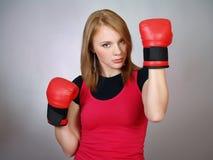 schönes starkes Mädchen in den roten Handschuhen für Verpacken lizenzfreie stockfotografie
