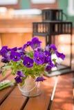 Schönes Stiefmütterchen in einem Blecheimer als Gedeckdekoration Nette Blumen und eine Laterne auf dem Holztisch draußen Stockfotos
