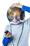 Schönes stilvolles blondes Kind, das große Berufskopfhörer und lustige Gläser trägt Lizenzfreies Stockfoto