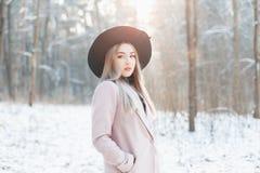 Schönes stilvolles junges Mädchen in einem modernen schwarzen Hut und in einem Mantel lizenzfreies stockbild