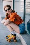 schönes stilvolles Mädchen in der Sonnenbrille und in Rollschuhen, die auf Treppe und dem Lächeln sitzen lizenzfreie stockbilder