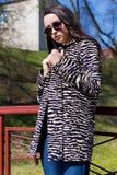 Schönes stilvolles Mädchen geht in den Park in der Sonnenbrille im Vorfrühling an einem sonnigen hellen Tag Stockfoto