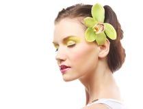 Schönes stilvolles Mädchen mit Orchideenblume im Haar Stockfoto