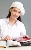Schönes Studentenmädchen, das ein Barett trägt. Stockfotos