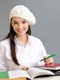 Schönes Studentenmädchen, das ein Barett trägt. Stockfotografie
